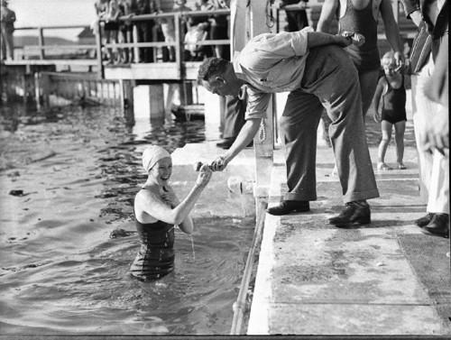 03+An+official+hands+a+young+woman+swimmer+a+token